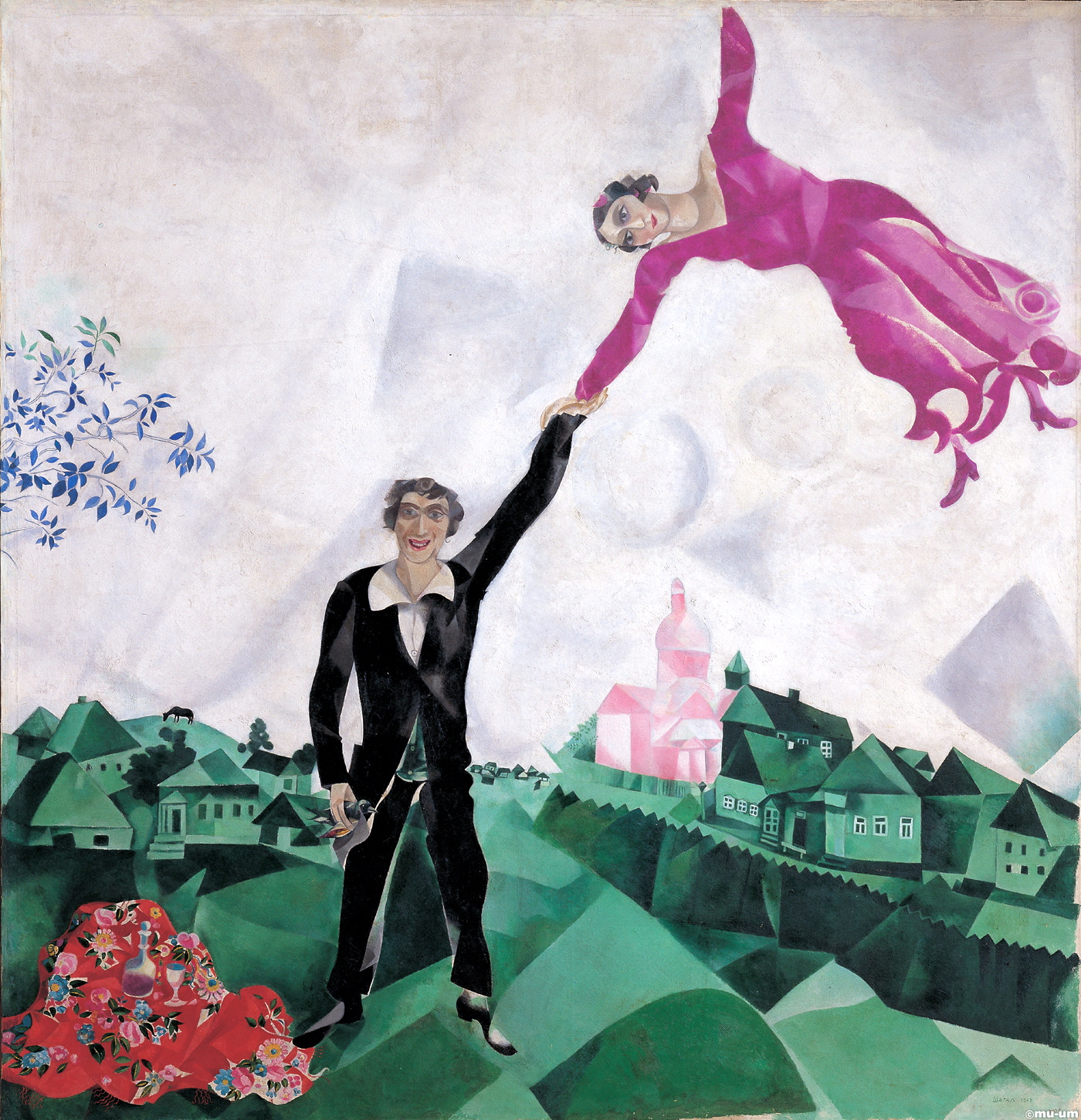 "Marc Chagall [French, born Russia (present-day Belarus), 1887-1985]: Over the Town, 1918. Oil on canvas, 45 x 56 cm. The State Tretyakov Gallery, Moscow, Russia. 'In his painting Over the City, Chagal and his wife Bella appear to be flying over Vitebsk while leaving in the space of Earth's gravity the little houses sinking to one side. The principle theme of Chagal's work is ""the time of man."" He understood this to mean ""man and his recollections, his reflections as something at the same time both existing and visible. It is a single being. And I portray it."" Therefore, the place allotted to any of the personages does not need to follow any laws of logic or physics and the figurative world loses its self-sufficiency and becomes only a pretext for expressing experiences. His ability to combine the lofty with the ordinary was one of the specific qualities of Chagal's art. Even when depicting two lovers hovering over the city and daily life, the artist does not forget about details. Bella's slippers, the lace of her dress, the very prosaic scene from life – all of this does not detract from the sense of the flight of these souls in love.' (© The State Tretyakov Gallery)"