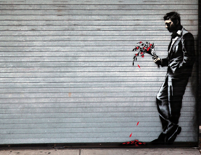 "Banksy (United Kingdom-based; graffiti artist, street art, political activist, film director, and painter): ""Waiting in vain...at the door of the club"" (Man with Flowers), 2013. Seen on a roll-down security gate covering the main entrance to Larry Flint's Hustler Club in Hell's Kitchen, New York, NY."